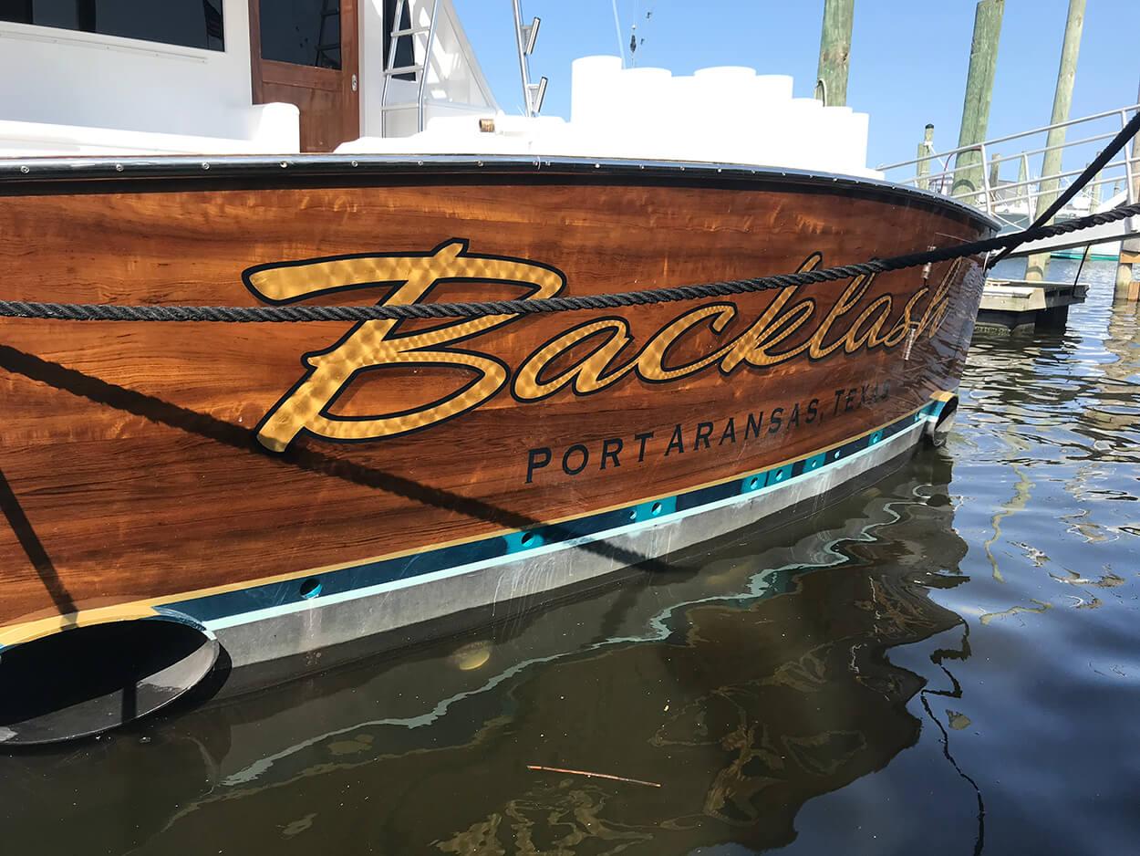 Backlash Port Aransas Texas Boat Transom in water wanchese engine turn gold leaf