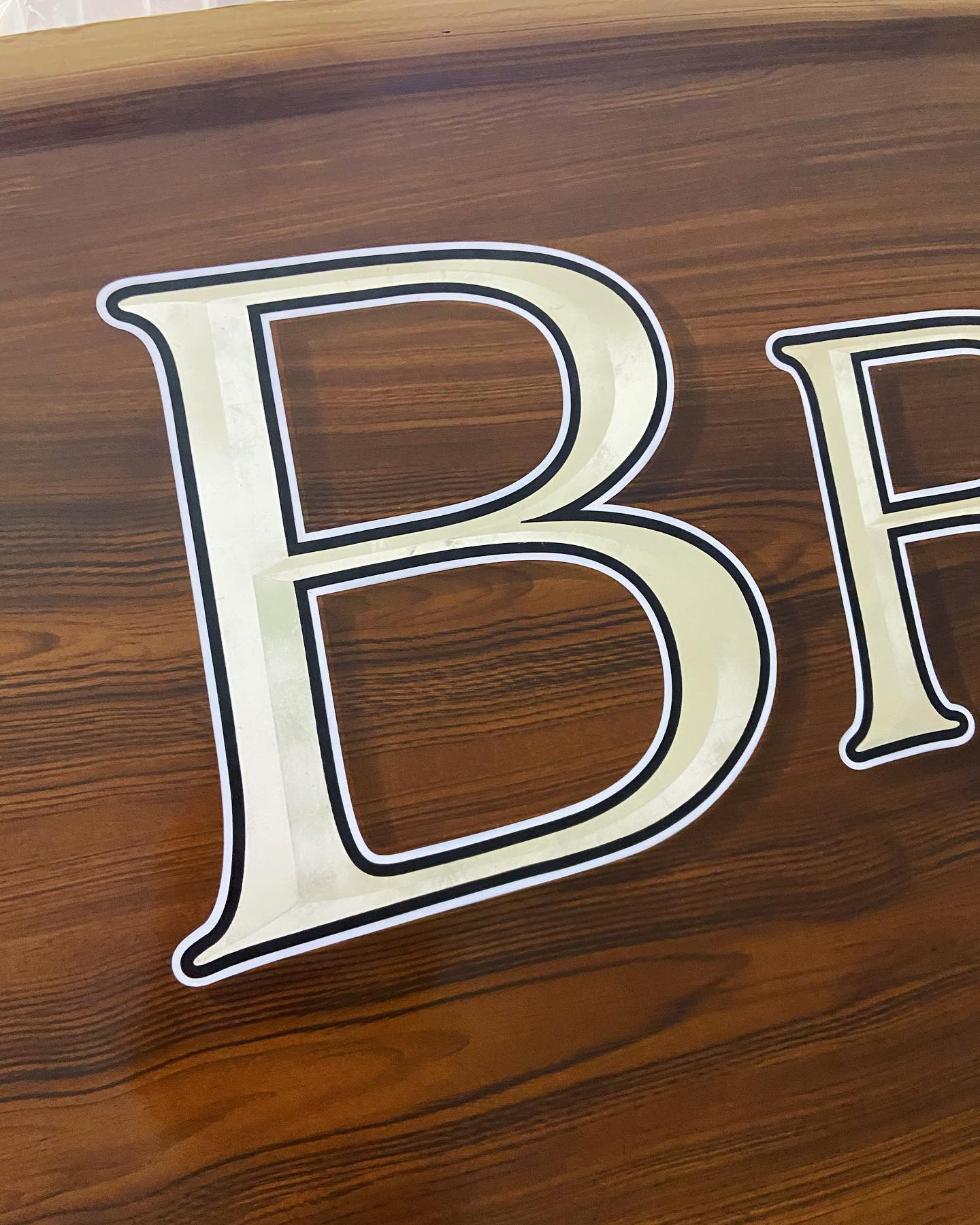 "Sneak peek at a freshly painted faux transom featuring a white gold leaf name for ""Brennan's Grin"", a 67' F&S at American Boatworks. @fsboatworks@americancustomyachts"