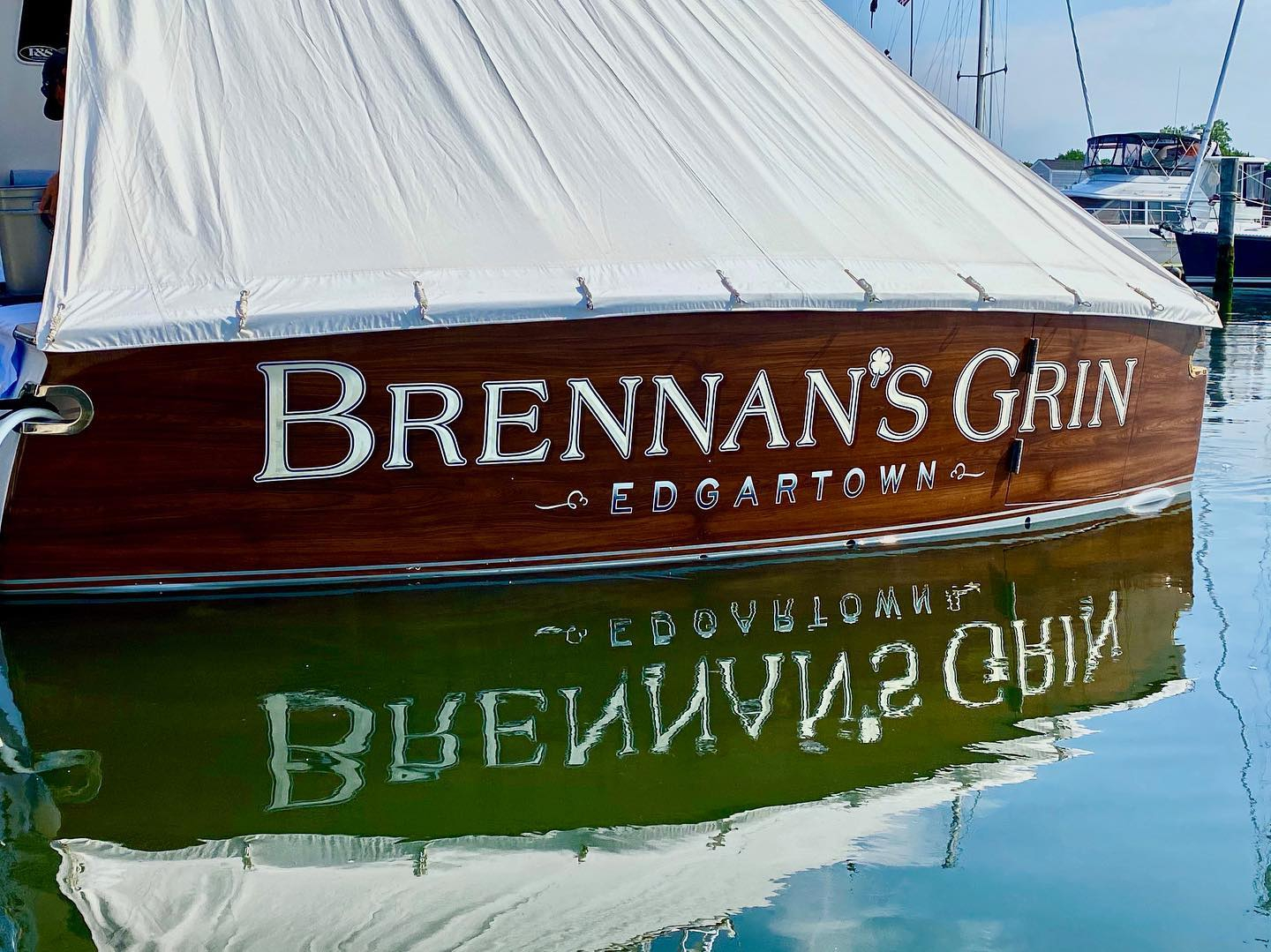 """""""Brennan's Grin"""" in her home waters of Edgartown, MA. This transom features our white gold, bevel style lettering, custom hailing ports, and faux teak transom."""