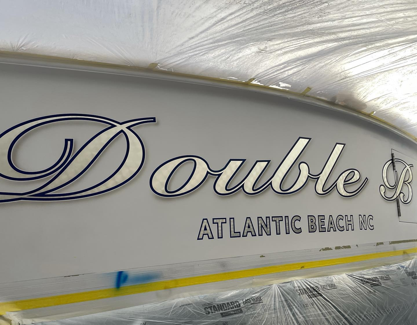Double B was recently painted by Everett Nautical in early 2020. This custom script name features engine turned white gold leaf with blue painted outlines and soft drop shadows. All work completed at Winter Custom Yachts, in Hubert, NC.